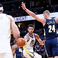 04 November 2017: Golden State Warriors guard Stephen Curry (30) passes the ball to Golden State Warriors center JaVale McGee (1) past Denver Nuggets center Mason Plumlee (24) during the Golden State Warriors 127-108 victory over the Denver Nuggets, at the Pepsi Center, Denver, Colorado, USA.