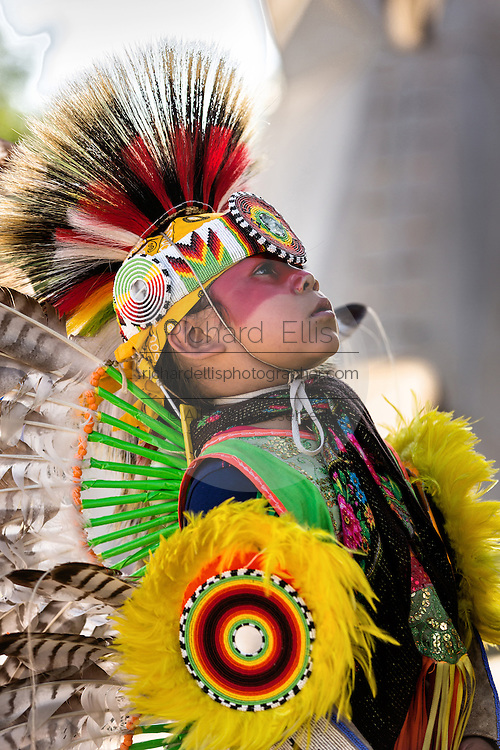 A young Native Americans dancer from the Arapahoe people dressed in traditional costume waits to perform at the Indian Village during Cheyenne Frontier Days July 25, 2015 in Cheyenne, Wyoming. Frontier Days celebrates the cowboy traditions of the west with a rodeo, parade and fair.