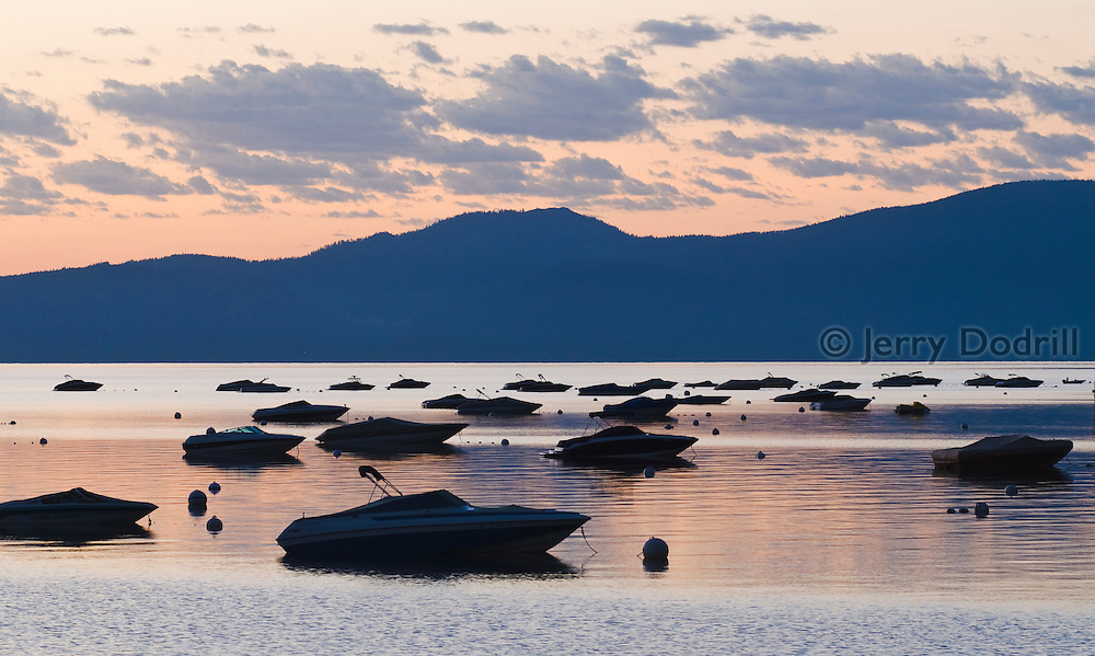Speed boats at their moorings along Lake Tahoe's western shoreline. Lake Tahoe is a large freshwater lake in the Sierra Nevada range on the California/Nevada Border. At a surface elevation of 6,225 ft Lake Tahoe is the largest alpine lake in North America with a depth of 1,645 ft.