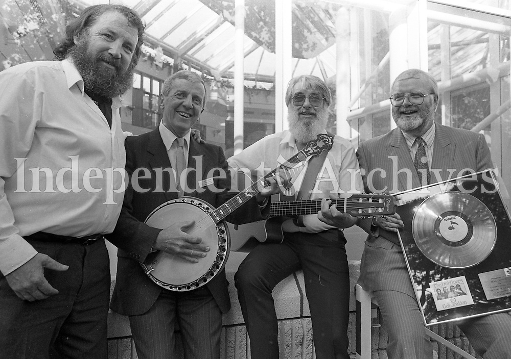 Barney McKenna helps Alan Glynn, General Manager of Jury's Hotel in Dublin to play a duet with Ronnie Drew as The Dubliners were presented with a Platinum Disc in honour of their achievements by Jack MacNiece, Managing Director of Harmac Music, presented at the New Dubliners Bar in Jury's, 21/07/1987 (Part of the Independent Nespapers Ireland/NLI Colection).