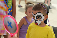 Brooklyn, New York, USA. 10th August 2013. GABRIEL RODRIGUEZ, 4, from Manhattan, looks in the mirror at the humorous puppy face that volunteer artist Laura painted for him, during the 3rd Annual Coney Island History Day celebration.