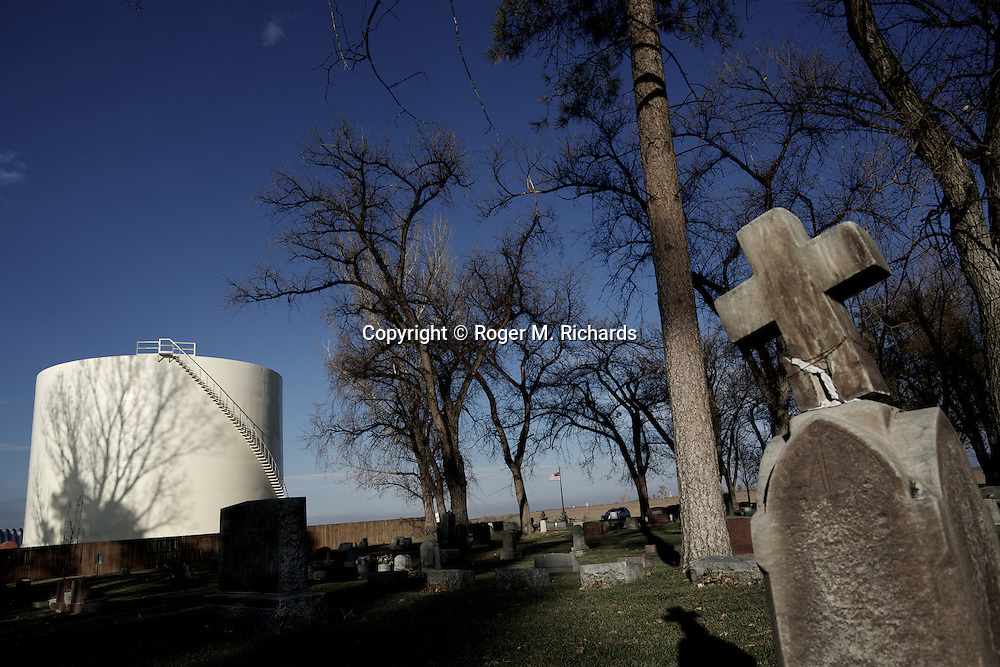 A cemetery in the high desert gains a neighbor of a natural gas storage tank in Weld County, Colorado. A boom in oil and gas drilling across the American West has led to pollution and environmental problems in what were once pristine lands. Traveling rigs go from location to location, drilling down into the shale rock, and are soon followed by pumps that inject a toxic brew of water and chemicals for hydraulic extraction or 'fracking' of oil and gas. Photograph by Roger M. Richards
