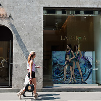 MILAN, ITALY - JULY 03:  A man and a woman walk in front of a sale sign in the fashion district of Milan on July 3, 2010 in Milan, Italy. Milan's summer sales start today. .***Agreed Fee's Apply To All Image Use***.Marco Secchi /Xianpix. tel +44 (0) 207 1939846. e-mail ms@msecchi.com .www.marcosecchi.com