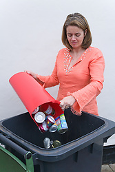 Woman putting tins and cans into recycling wheelie bin ready for collection,