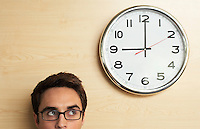 Cropped image of young businessman in glasses looking up to office clock