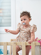 1 year old baby girl stands in her cot (or crib)