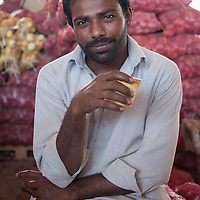 A South Asian migrant worker takes a tea break at a wholesale produce warehouse on the outskirts of Muscat.