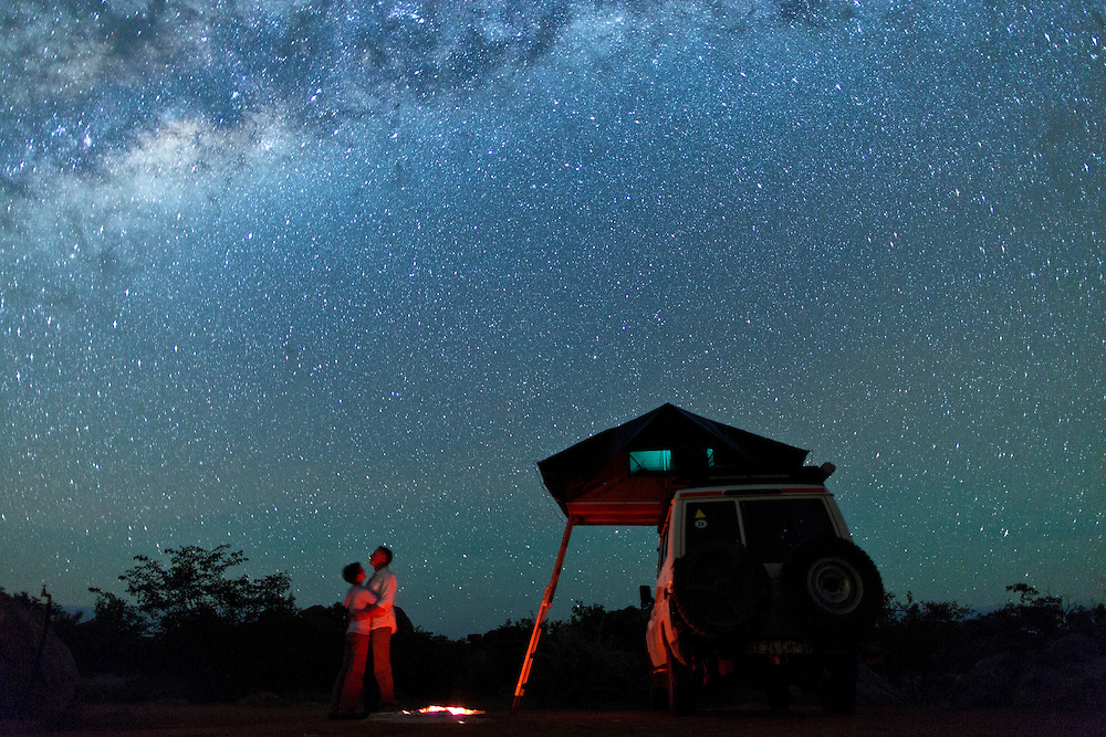 A couple stands under the stars next to their 4x4 vehicle with a tent on the top, and a campfire.