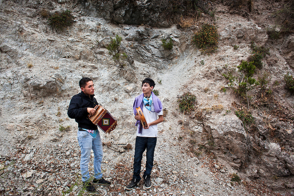 Polsi, Italy - 2 September, 2012: Francesco, 15, and Giuseppe, 14, play accordion and tambourine on their way back from the Sanctuary of Our Lady of Polsi, a mafia stronghold in Calabria, Italy, on September 2nd, 2012. <br /> The Sanctuary of Our Lady of Polsi, also known as the Sanctuary of Santa Maria di Polsi or Our lady of the Mountain, is a Christian sanctuary in the heart of the Aspromonte mountains, near San Luca in Calabria. The chiefs of the Calabrian criminal consortium, the 'Ndrangheta, have held annual meetings at the Sanctuary. According to the pentito Cesare Polifroni &ndash; a former member turned state witness &ndash; at these meetings, every boss must give account of all the activities carried out during the year and of all the most important facts taking place in his territory such as kidnappings, homicides, etc.<br /> <br /> Calabria is one of the poorest Italian regions which suffers from lack of basic services (hospitals without proper equipment, irregular electricity and water), the product of disparate political interests vying for power. The region is dominated by the 'Ndrangheta (pronounced en-Drang-get-A), which authorities say is the most powerful in Italy because it is the welthiest and best organized.<br /> <br /> The region today has nearly 20 percent unemployment, 40 percent youth unemployment and among the lowest female unemployment and broadband Internet levels in Italy. Business suffer since poor infrastructure drives up transport costs.<br /> <br /> Last summer the European Union's anti-fraud office demanded that Italy redirect 380 million euros in structural funding away from the A3 Salerno - Reggio Calabria highway after finding widespread evidence of corruption in the bidding processes.