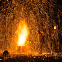 Nov. 2, 2013 - Lexington, Ky, USA - Wearing protective fire suits, University of Kentucky students and faculty and guest artists are showered by sparks as they pour molten iron into casts during UK's Sculpture iron pour. Each year, the art department invites the public to watch them melt iron into a molten liquid and pour it into forms where it solidifies and becomes a piece of art. The culmination of the event is a spark-filled iron pour into wooden casts by Louisville sculptor Andrew Marsh. (Credit Image © David Stephenson/ZUMAPRESS.com)