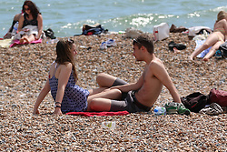 © Licensed to London News Pictures. 19/05/2014. Brighton, UK. A couple sunbathing on Brighton beach. The hot weather is continuing with record temperatures all around the UK. The beach in Brighton attracted hundreds of sun seekers. Photo credit : Hugo Michiels