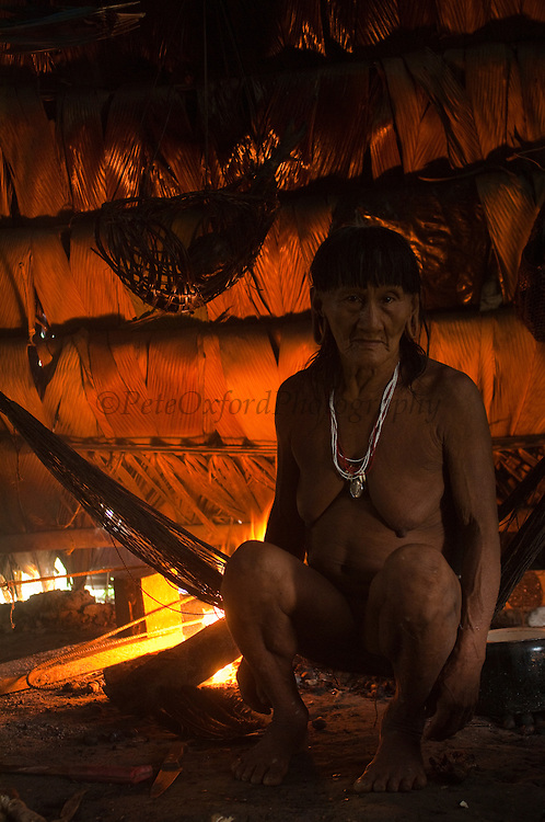 Huaorani Indian, Me&ntilde;emo Bopoga making fire while sitting in her hammock.<br /> Bameno Community. Yasuni National Park.<br /> Amazon rainforest, ECUADOR.  South America<br /> This Indian tribe were basically uncontacted until 1956 when missionaries from the Summer Institute of Linguistics made contact with them. However there are still some groups from the tribe that remain uncontacted.  They are known as the Tagaeri &amp; Taromenane. Traditionally these Indians were very hostile and killed many people who tried to enter into their territory. Their territory is in the Yasuni National Park which is now also being exploited for oil.