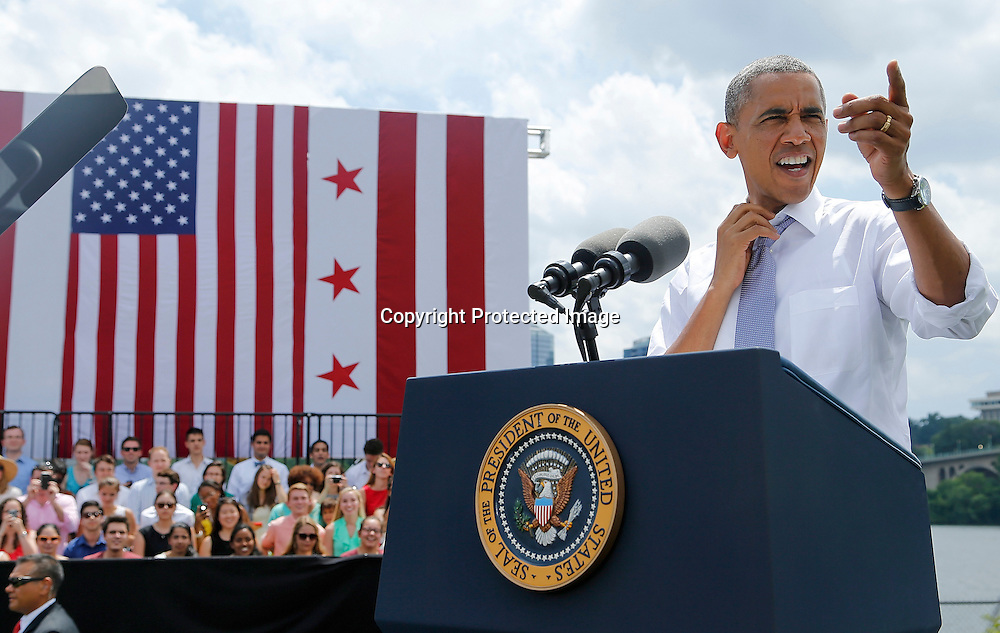 U.S. Presidnet Barack Obama loosens his tie in the heat before he delivers remarks on the economy at the Georgetown Waterfront Park in Washington July 1, 2014.
