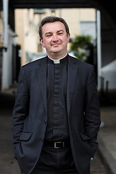 © Licensed to London News Pictures. 23/05/2016. LONDON, UK.  Priest-in-Charge of St George-in-the-East church, Angus Ritchie attends the unveiling of a billboard located opposite the Jack the Ripper museum in Cable Street, Tower Hamlets, advertising a new pop-up museum, 'East-End Women: The Real Story'. Following and opposition and protests against the controversial Jack the Ripper museum, which had promised to celebrate east end women, but activists opposed and claimed glorified violence against women, the museum is a response by the East End Women's Collective, with funding from 38 Degrees members, which aims to celebrate east end women who have stood up for women's rights and against violence. The museum will open at St George-in-the-East church from 26th May to 9th July.  Photo credit: Vickie Flores/LNP