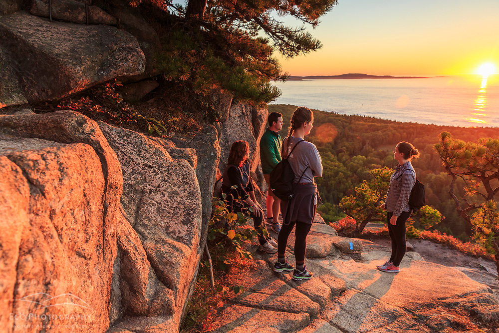 "Hikers watch the sunrise from a ledge on ""The Beehive"" in fall in Maine's Acadia National Park."