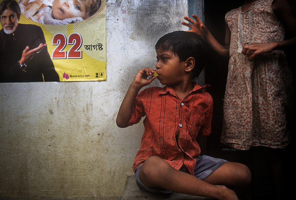 A child on Sagar Island plays with a plastic whistle that he received after being vaccinated for polio. The Volunteers sometimes give away small gifts to attract the children to the booth to take the vaccine. On the wall, a poster with the date of the NID (National Immunization Day). West Bengal, August 22, 2004.