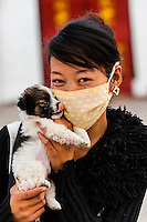 Chinese woman holding puppy, Barkhor Square, Lhasa, Tibet (Xizang), China.