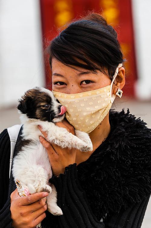 Chinese woman holding puppy, Barkhor Square, Lhasa, Tibet (Xizang), China.