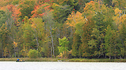 Susan Lake, near Charlevoix Michigan, is an idyllic setting, with only a modest amount of development. This lone canoeist and the beautiful tree provide no hint of the bustling city only a few miles to the west.