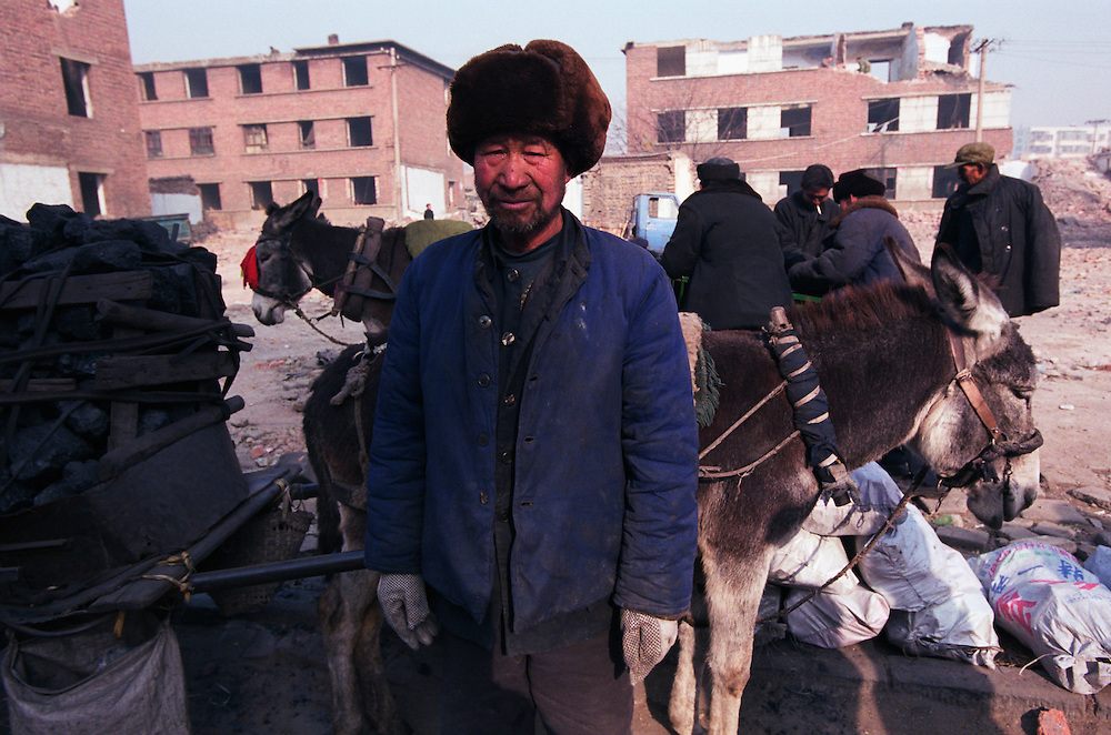 Donkey cart coal sellers in a city street. The sellers buy coal from the mines at 4 AM, transport the coal 20 kms to the city center to sell for domestic heating and cooking use. They earn about 100 RMB (10 ¤) per day. 75% of China's growing energy needs is supplied by coal, the cheapest and dirtiest form of energy. China is the world's largest producer of coal. Seven of the world's ten most polluted cities are in China, largely due to coal use and the country's dilapidated heavy industries..Dàtóng, Shanxi Province, China. 12/11/2005.Photo © J.B. Russell