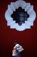 Mayan woman walks beneath a window in Antigua, Guatemala