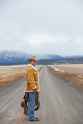 cowboy with a saddle standing on a dirt road in the mountains