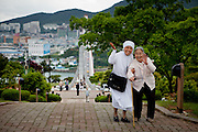 "Nun guiding an elderly woman to a mountain top during an organised excursion for old people to the city of Yeosu. Yeosu will host the Expo 2012 exhibition  under the theme ""The Living Ocean and Coast"". Yeosu (Yeosu-si) is a city in South Jeolla Province. Old Yeosu City, which was founded in 1949, Yeocheon City, founded in 1986, and Yeocheon County were merged into a new city in 1998."