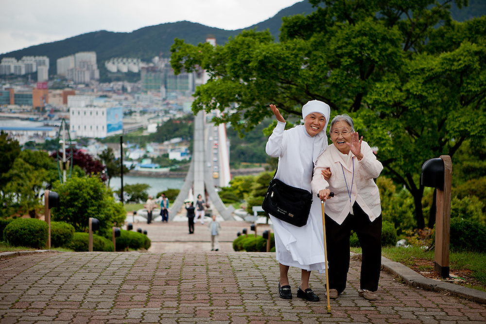 """Nun guiding an elderly woman to a mountain top during an organised excursion for old people to the city of Yeosu. Yeosu will host the Expo 2012 exhibition  under the theme """"The Living Ocean and Coast"""". Yeosu (Yeosu-si) is a city in South Jeolla Province. Old Yeosu City, which was founded in 1949, Yeocheon City, founded in 1986, and Yeocheon County were merged into a new city in 1998."""