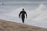 Surfer walking along the tide line at the Marconi Beach, Cape Cod, Massachusetts, USA, September 3, 2011.