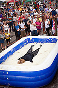 A participant in the Grits Roll wallows in a pool of grits during the annual World Grits Festival in St George, SC