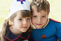 Girl and boy dressed up as Nurse and Superhero in park portrait