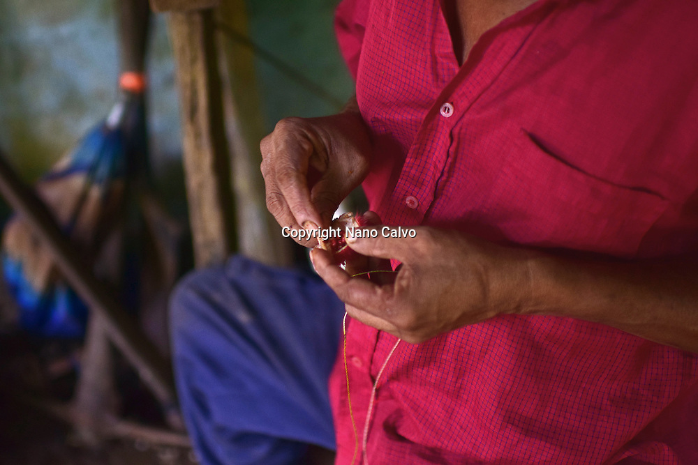 Catato López, Bribri man working on handmade necklace. A day with the Bribri, indigenous people in Limón Province of Costa Rica