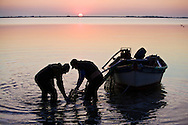 Fishermen, collectiong clams, work in the nearby of a very big elettricity industry. The industry pollutes the water with nanoparticels. Clams are consequentially polluted. This area, Polesine, supplies the major percentage of clams and mussels in Italy, and a big part of the production is for export.