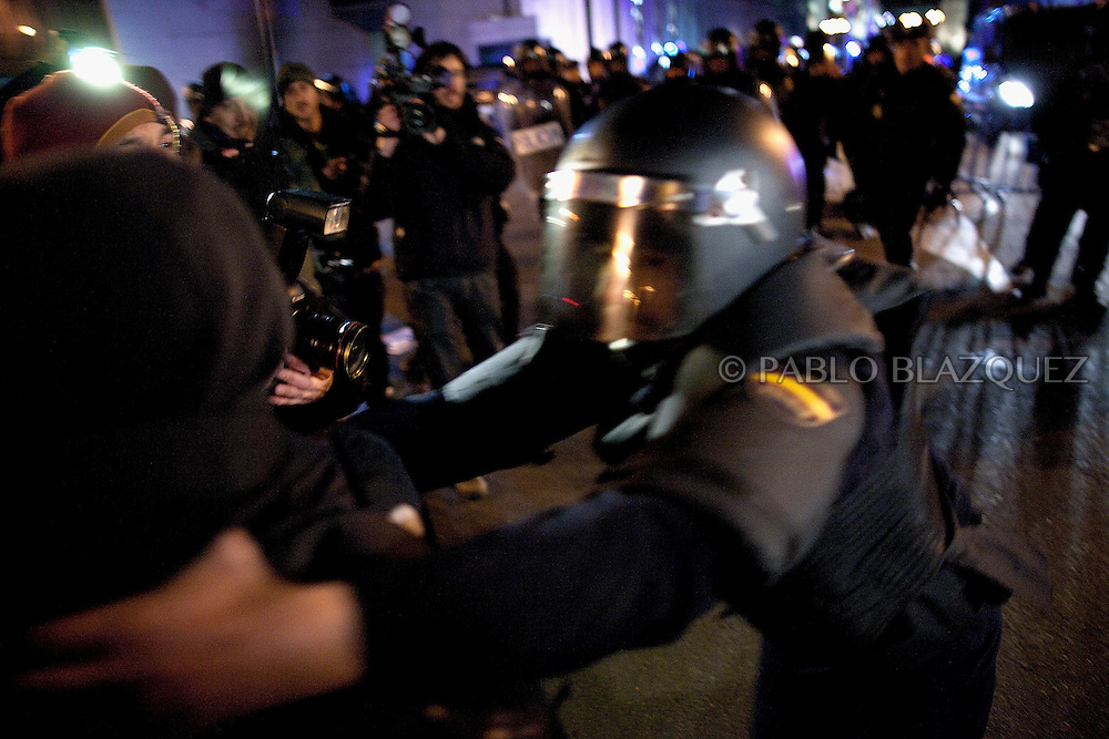 A policeman grab a protester during clashes following a demonstration organized by Spain's 'indignant' protesters at the Puerta del Sol square in Madrid on February 10, 2012, hours after Spain's right-leaning government unveiled a labour reform. The number of jobless people in Spain shot above five million at the end of 2011, sending the unemployment rate to 22.85 percent -- double the European average and the highest in the industrialized world. Placard reads 'Against the labour reform.'