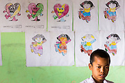 04 MARCH 2014 - MAE SOT, TAK, THAILAND: A boy stands in front of a wall decorated with his classmates' art work at the Blue Sky School in Mae Sot. There are approximately 140 students in the Sky Blue School, north of Mae Sot. The school is next to the main landfill for Mae Sot and serves the children of the people who work in the landfill. The school relies on grants and donations from Non Governmental Organizations (NGOs). Reforms in Myanmar have alllowed NGOs to operate in Myanmar, as a result many NGOs are shifting resources to operations in Myanmar, leaving Burmese migrants and refugees in Thailand vulnerable. The Sky Blue School was not able to pay its teachers for three months during the current school year because money promised by a NGO wasn't delivered when the NGO started to support schools in Burma. The school got an emergency grant from the Burma Migrant Teachers' Association and has since been able to pay the teachers.    PHOTO BY JACK KURTZ
