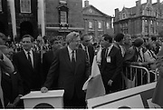 Nissan International Cycle Race..1986..01.10.1986..10.01.1986..1st October 1986..The Nissan Classic began today from Trinity College,Dublin. The offical race starter was The Taoiseach,Dr Garrett FitzGerald TD. He was accompanied by the Minister for Sport,Mr Sean Barrett TD..Sean Kelly was returning to defend his title but his opposition included Greg LeMond, the 1983 world champion and the winner of the Tour de France of the previous July. Roche was out due to his injured leg. Adri van der Poel was back with 1980 Tour de France winner and 1985 world champion Joop Zoetemelk. Teun van Vliet was back too. The winner of the green jersey of the Tour de France that July, Eric Vanderaerden was there as well as Australians Phil Anderson and Alan Peiper as well the Scottish cyclist Robert Millar...Image of An Taoiseach,Dr Garret FitzGerald,with the Irish Tricolour which would be used to start the race.