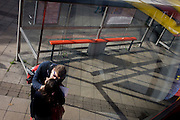 Kissing couple and aerial view of bus stop shadows and reflections.