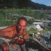 Duncan Murrell eating his breakfast of huckleberry pancakes at Point Hayes, Chichagoff Island, Southeast Alaska, USA.<br />
