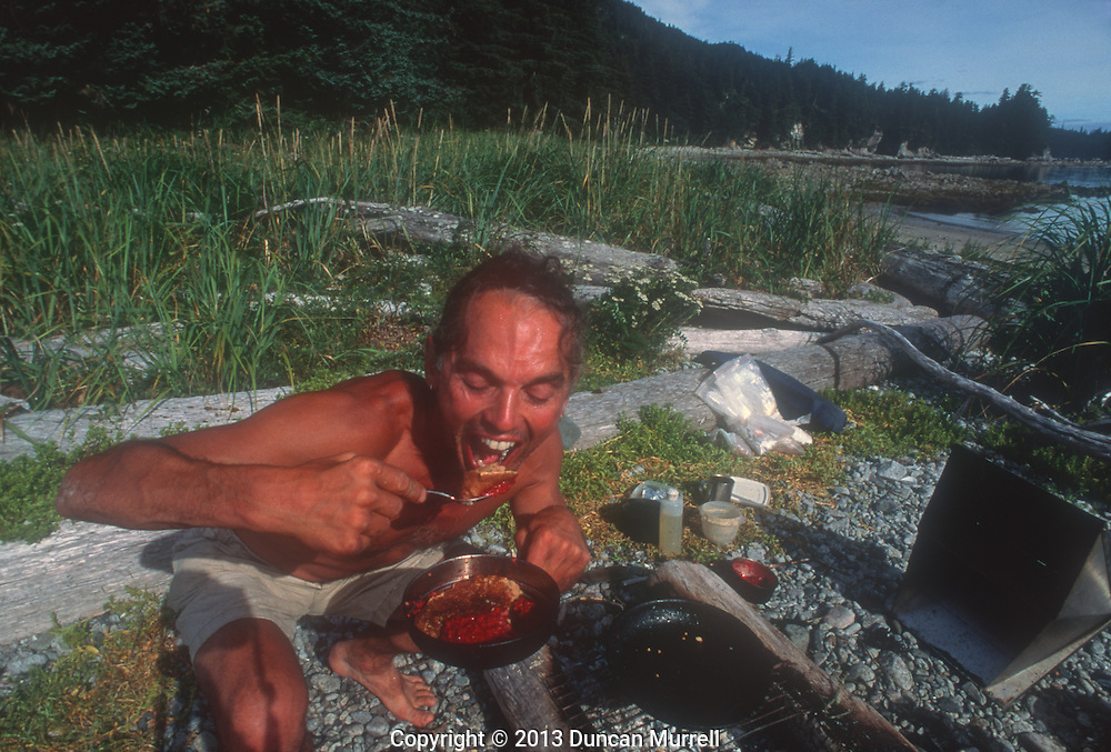 Duncan Murrell eating his breakfast of huckleberry pancakes at Point Hayes, Chichagoff Island, Southeast Alaska, USA.<br /> <br /> This was my main camp for many years when I was photographing the bubble net feeding humpback whales. It was a perfect lookout point enabling me to look up and down Chatham Strait, which is the longest navigable channel in the USA. It's also the point where the Peril Straits enters Chatham Strait from the Pacific Ocean to the west. It was a perfect camp site in many ways apart from being near one of the whales' favourite feeding sites, the Morris Reef. It had two protected beaches for ease of launching and landing, facing either north or south, depending on which way the wind was blowing from. It was close to streams for fresh water and there was always plenty of firewood washed up on the shore. Perhaps my favourite reason was that in the forest nearby was the biggest patch of huckleberry bushes that I knew of, and huckleberries were my favourite berries to have on my stack of pancakes every morning, to fuel me up for another long hard day paddling with the whales.<br /> It was also a beautiful spot to eat my dinner in the evening. I cooked very elaborate dinners because that was evening's entertainment every night. Every night I would slide back into my reclining camp seat and watch the dying embers of the fire flicker beneath the stars, and the moon cross Chatham Strait from Admiralty Island to Baranof Island. The stillness of the night was periodically punctuated by a gentle volley of whale breath, which perfectly complemented the sounds of contentment rumbling inside my full belly.