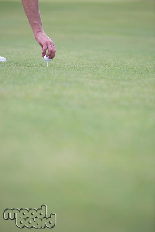 Hand placing ball on golf tee