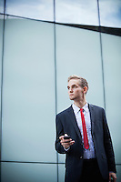 Young businessman with cell phone standing against glass building