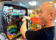 Garden City, New York, USA. December 12, 2015. DANNY TORRES holds his 19-month-old son MATEO TORRES, from Lindenhurst, as they point to yeti-like aliens on the Midway Bally 1980 video game Deluxe Space Invaders, which the dad played during Opening Day of Arcade Age exhibit, at Cradle of Aviation Museum in Long Island. Admission includes unlimited free pay-to-play of video arcade games, and games history is displayed outside arcade area. Exhibit runs from Dec. 12, 2015 through April 3, 2016.