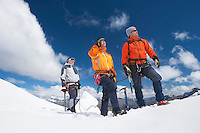 Three mountain climbers on snowy peak