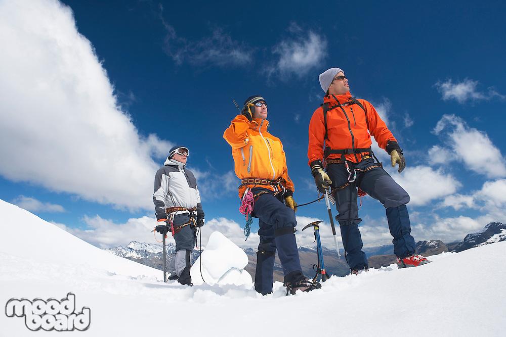 Three mountain climbers on snowy peak