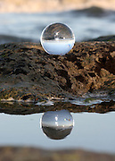 Crystal ball on a rock reflecting in a tidal pool on a Jekyll Island beach