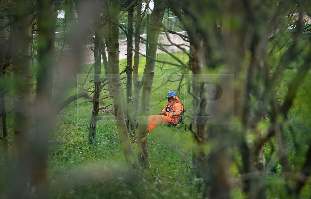 © Licensed to London News Pictures. 28/04/2019. London, UK. A security guard rests as he keeps watch over High Speed 2 works in the Colne Valley west of London. Extinction Rebellion activists have joined with Stop HS2 protestors to occupy trees in Colne Valley to stop their felling for the HS2 rail project. Workers were expected to start cutting down the trees yesterday and to continue today but the protests have stopped the work. Photo credit: Peter Macdiarmid/LNP