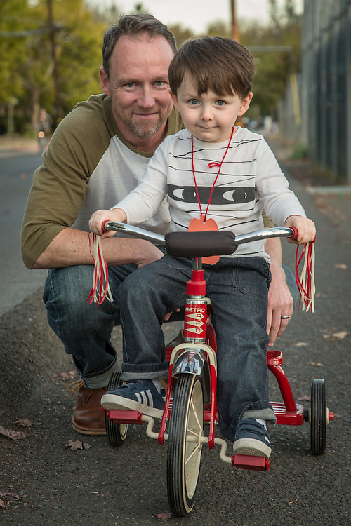 "Michael Swenton with his 3 year old son, Henry, who is riding his tricycle for the first time near Calistoga High School.  ""A friend gave us this tricycle when Henry was born...it wasn't until tonight that he has ridden it outside the house."""