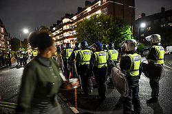 © Licensed to London News Pictures. 03/07/2020. London, UK.  A woman back at riot police reacting to a block party that moved through boroughs in west London ending in White City estate in the early hours of July 4th. A date that coincides with relaxing of rules, dubbed ëSuper Saturdayí, permitting pubs and restaurants to serve alcohol for first time since restrictions were imposed earlier in the year in response to the coronavirus pandemic. Photo credit: Guilhem Baker/LNP