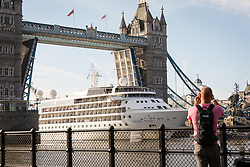 © Licensed to London News Pictures. 01/08/2017. LONDON, UK.  A man photographs Silver Wind, a huge 514 feet long, 17,400 ton cruise liner as she leaves London under Tower Bridge this morning after a brief visit, towed backwards by two tugs. Silver Wind carries just 296 passengers and its owner, Silversea claim that the ship has amongst the highest space-to-guest ratios in the cruise ship industry, with the largest suites measuring 1,314 square feet. Tickets cost thousands of pounds, but all guest expenses, even champagne are included in the price. Environmentalists claim thepollutioncreated by giantcruise ships outweigh their economic benefits. The Port of London Authority (PLA) are conducting a work programme during 2017 to monitor air quality and pollution caused by river traffic on the River Thames.  Photo credit: Vickie Flores/LNP