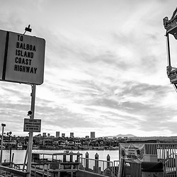 Newport Beach California Balboa Fun Zone high resolution sunrise black and white panoramic photo. Includes the Balboa Island Auto Ferry sign, Ferris Wheel, Newport Harbor, and Balboa Island. Newport Beach is a popular coastal city along the Pacific Ocean in Orange County Southern California. Copyright ⓒ 2017 Paul Velgos with All Rights Reserved.
